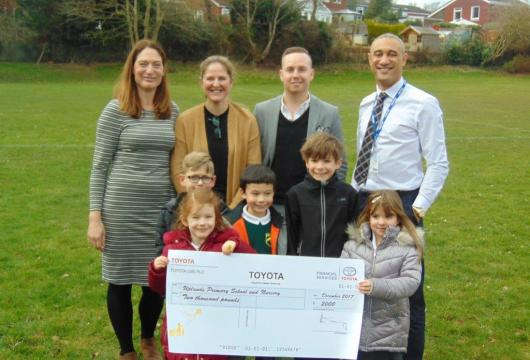 Jason Harrison, General Manager and Lorna Bye, VCI Champion from Inchcape Toyota Sandhurst present a cheque for £2,000 to Uplands Primary School to create new outdoor learning areas.